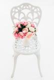 在伪造的葡萄酒椅子的美丽的花束牡丹在绝尘室 免版税库存照片