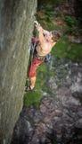 在伸出的峭壁的肌肉攀岩运动员攀登 免版税库存照片