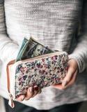 在伸出$ 100的妇女` s钱包上 花印刷品  妇女有好的修指甲的` s手 企业提议 免版税库存照片