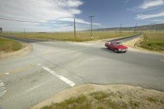 在位于沙漠的四条路的一个十字路口的一辆红色卡车在兰卡斯特,加州附近 图库摄影