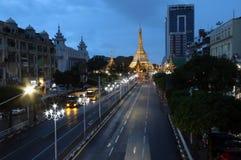 在位于街市仰光的心脏的苏拉树塔金黄八角形物的暮色时间 库存照片