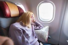 在位子的疲乏的白肤金发的偶然白种人夫人sleepin,当旅行乘飞机时 商业运输乘飞机 免版税库存照片