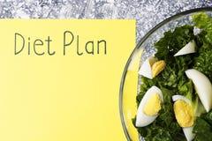 在低俗新闻和沙拉的题字用餐计划 在视图之上 免版税库存照片