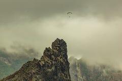 在低密集的云彩和山峰之间的偏僻的滑翔伞在加拉奇科附近,特内里费岛,西班牙村庄  库存照片