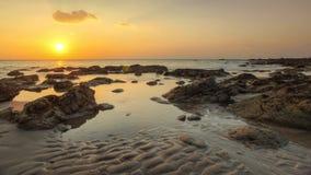 在低潮期间,靠岸在金黄日落光 库存图片