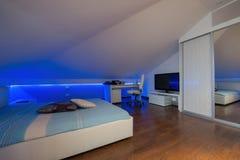 在低灯-射击的豪华顶楼公寓的卧室对highligh 免版税库存图片