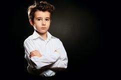 在低调的小男孩画象与横渡的胳膊 图库摄影