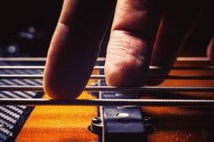 在低音吉他的男性手指 库存照片