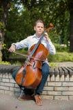在低音提琴的男孩playes 免版税图库摄影