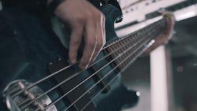 在低音构成的表现的期间低音吉他特写镜头 可看见的串和手 影视素材