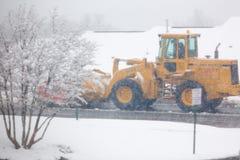 在住宅街道上的人大风雪犁清洁雪在冬天 免版税图库摄影