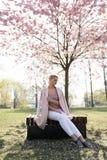 在佐仓樱花公园在春天享受自然和时间的美丽的白肤金发的年轻女人在她期间旅行 免版税库存照片