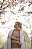 在佐仓樱花公园在春天享受自然和时间的美丽的白肤金发的年轻女人在她期间旅行 免版税库存图片