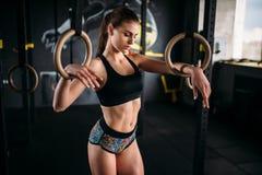 在体操圆环的亭亭玉立的女运动员锻炼 库存照片