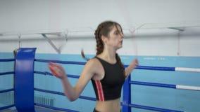 在体育俱乐部炫耀生活方式,健身妇女执行在拳击台的跳的锻炼 股票视频