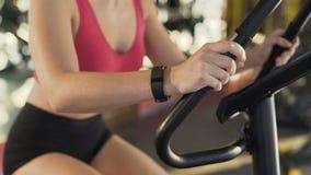 在体育俱乐部的健康亭亭玉立的女性佩带的健身镯子骑马锻炼脚踏车 股票视频