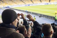 在体育场拍他们的手的爱好者 免版税图库摄影