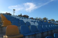 在体育场的空位椅子和奥运会的标志 库存照片