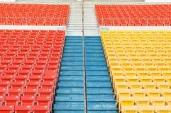 在体育场的空的橙色和黄色位子 库存照片