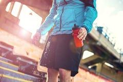 在体育场的运动员饮用水用很多水在阳光下滴下 免版税库存照片