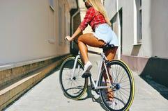 在体育样式的性感的妇女后面修理了室外齿轮的自行车 免版税库存照片