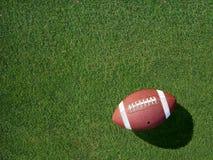 在体育草皮草有角度的左边的橄榄球 免版税图库摄影