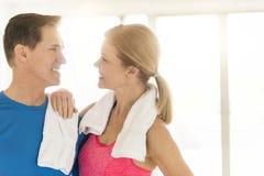 在体育衣物的愉快的成熟夫妇在家 免版税图库摄影