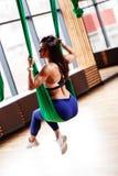 在体育衣裳打扮的美丽的年轻深色的女孩是在现代健身房的绿色空中丝绸 免版税库存照片