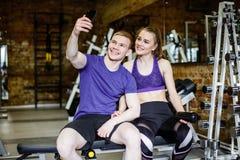 在体育衣裳的美好的愉快的夫妇做selfie使用一个巧妙的电话并且微笑着,当休息在锻炼以后时 免版税库存图片
