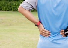 在体育锻炼跑的跑步以后供以人员遭受在他的背部受伤的痛苦 免版税库存图片