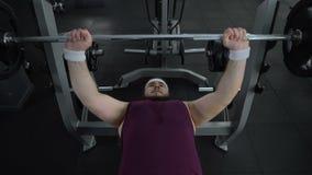 在体育锻炼,健康期间,无法胖的人举在健身房的重的杠铃 影视素材
