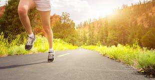 在体育鞋子的腿在日出的路 免版税图库摄影