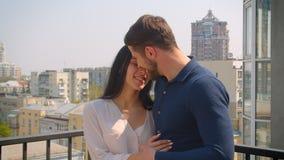 在体贴拥抱和亲吻在大阳台的爱的年轻白种人夫妇享受城市视图 股票录像