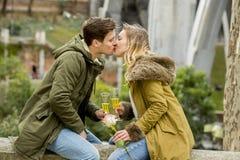 在体贴亲吻在街道上的爱的夫妇庆祝欢呼在香宾的情人节或周年 免版税库存照片