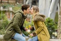 在体贴亲吻在街道上的爱的年轻甜夫妇庆祝欢呼在香宾的情人节或周年 免版税图库摄影