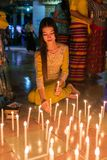 在佛教寺庙在Thadingyut期间或照明设备节日的美好的缅甸妇女火蜡烛在毛淡棉,缅甸 库存图片