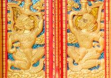 在佛教寺庙的红色门雕刻的hanuman金黄 库存图片