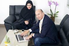 在佩带Hijab的一个资深商人&妇女之间的多种族业务会议 图库摄影