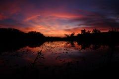在使变暗的蓝天的小束的橙色云彩 免版税库存照片
