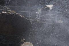 在使它的岩石的水飞溅湿 库存图片