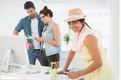 在使用三原色圆形图的同事前面的微笑的设计师 免版税库存图片