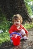 在使用与一个桶的河小女孩附近的夏天水 图库摄影