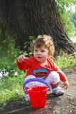 在使用与一个桶的河小女孩附近的夏天水 免版税库存图片