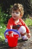在使用与一个桶的河小女孩附近的夏天水 免版税库存照片