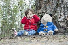 在使用与玩具熊的森林小女孩的春天 免版税库存照片