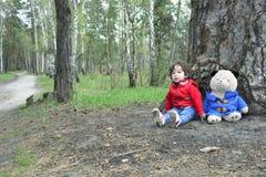 在使用与玩具熊的森林小女孩的春天 免版税库存图片