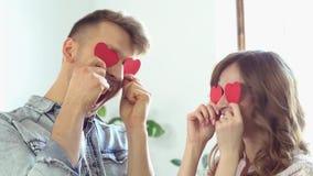 在使用与纸心脏的窗口附近的年轻夫妇在家一起圣徒华伦泰` s天概念 股票录像