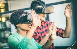 在使用与vr虚拟现实风镜的爱的多种族夫妇 库存图片