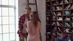 在使用互相的图书馆的年轻夫妇在家一起圣徒华伦泰` s天概念 股票录像