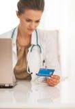 在使用信用卡的医生妇女的特写镜头 免版税库存图片